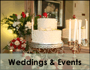 white wedding cake on stand in dining room along side flowers with caption