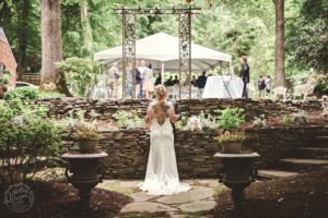 Bride standing looking at guests under tent from a rock garden area