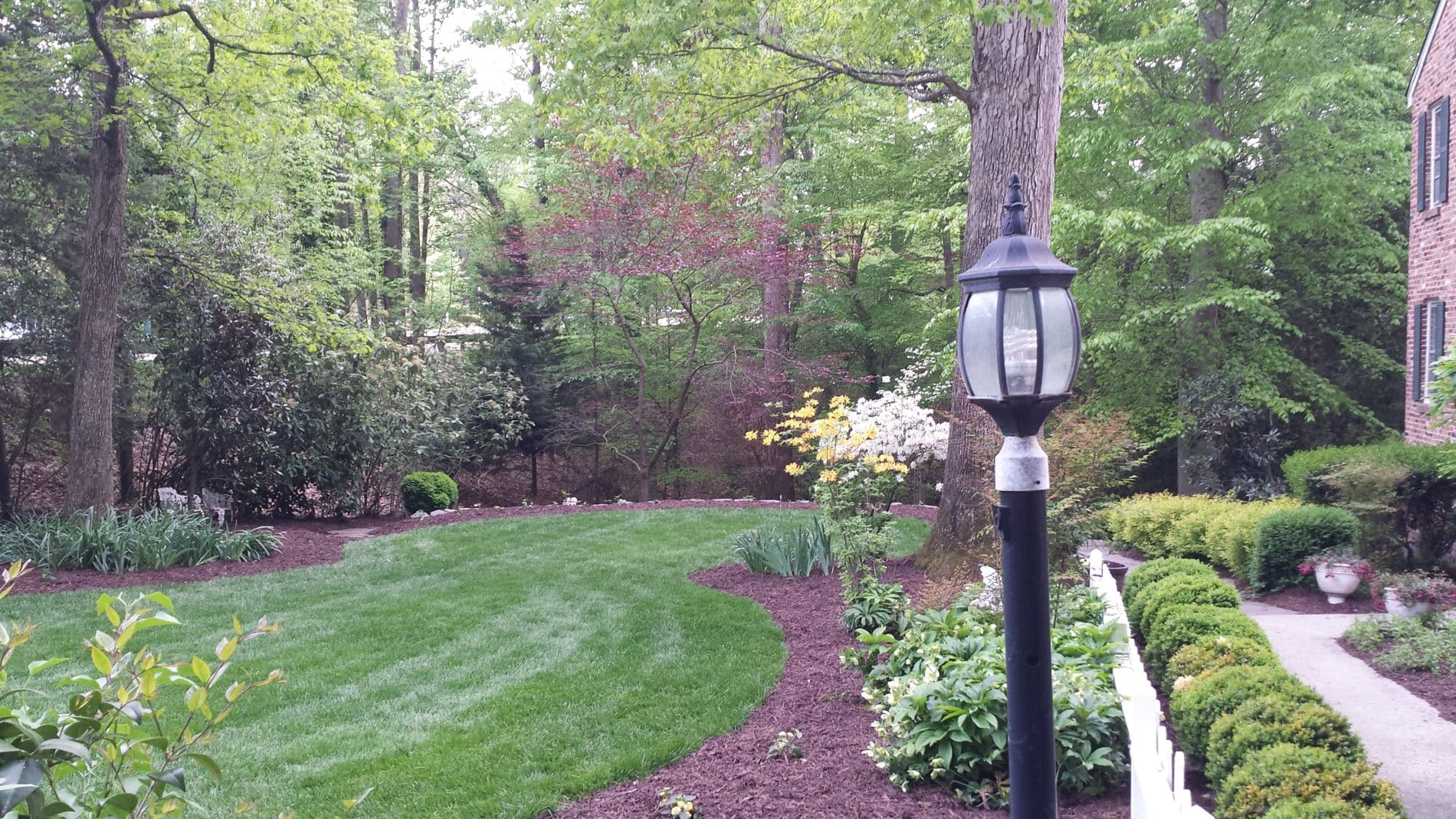 Green lawn in front of B&B with trees and bushes and black lamp post