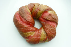 one pink and white bagel on a white background