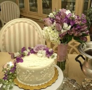 decorated wedding cake with purple flowers next to silver champane bucket and brides bouqet