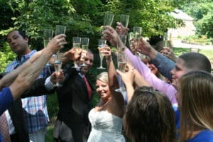 Bride and 10 guests in garden raising champagne glasses