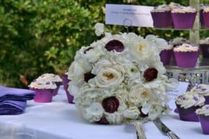 white and purple Bridal bouqet on table next to cake and cup cakes with purple holders