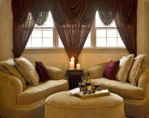 A room at Colonial Gardens B&B. Two cushioned seats with an ottoman below a burgundy draped windows.