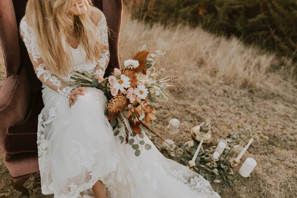 bride holding bouquet while sitting on a wooden chair in a field of grass