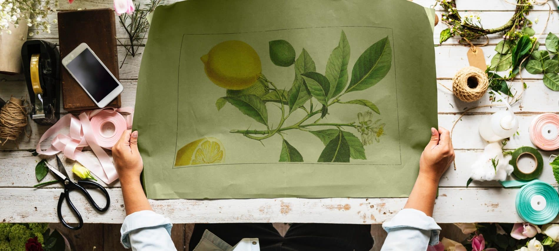 man standing in front of drafting table covered in flowers and holding a drawn sketch of a lemon tree branch