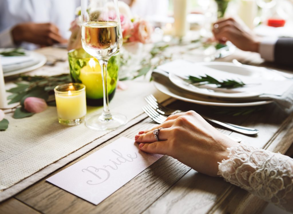 wooden wedding table with settings and a burlap table runner