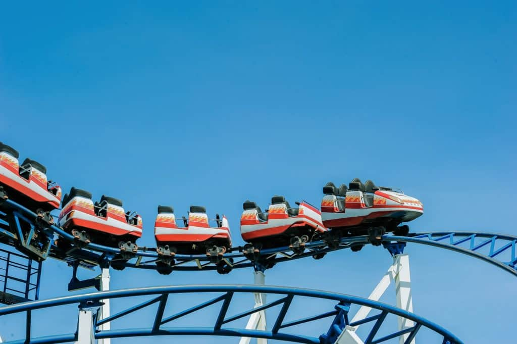 red roller coaster cars on the track on a clear day with blue skies in the background