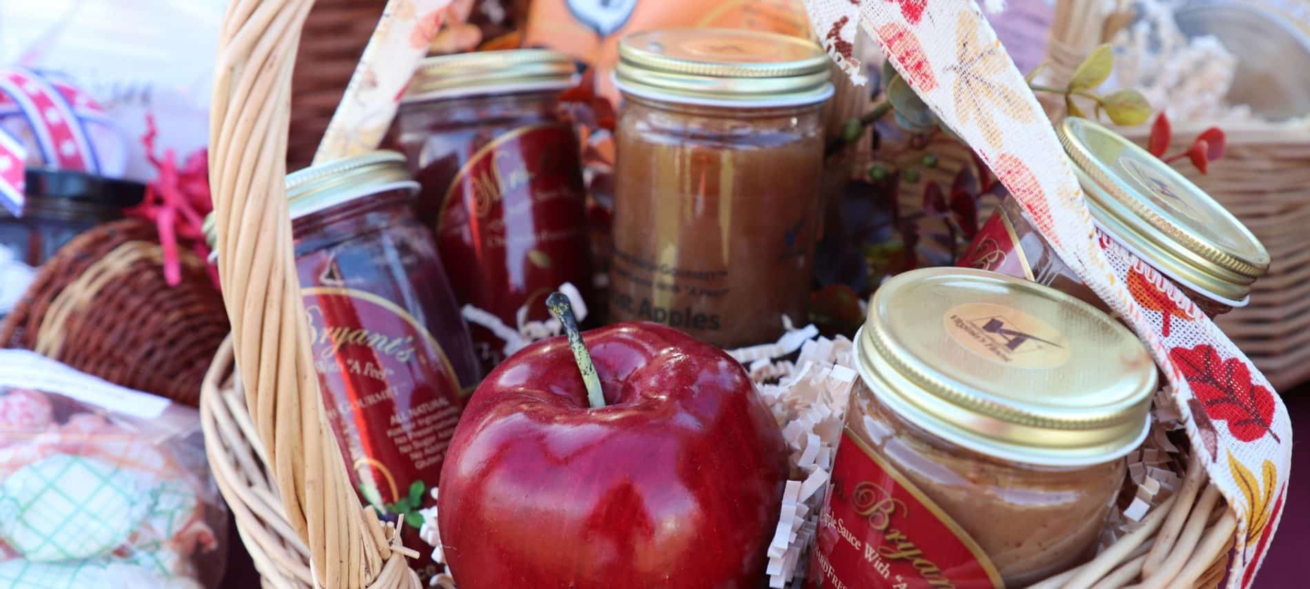 Basket full of red apples and fruit jams