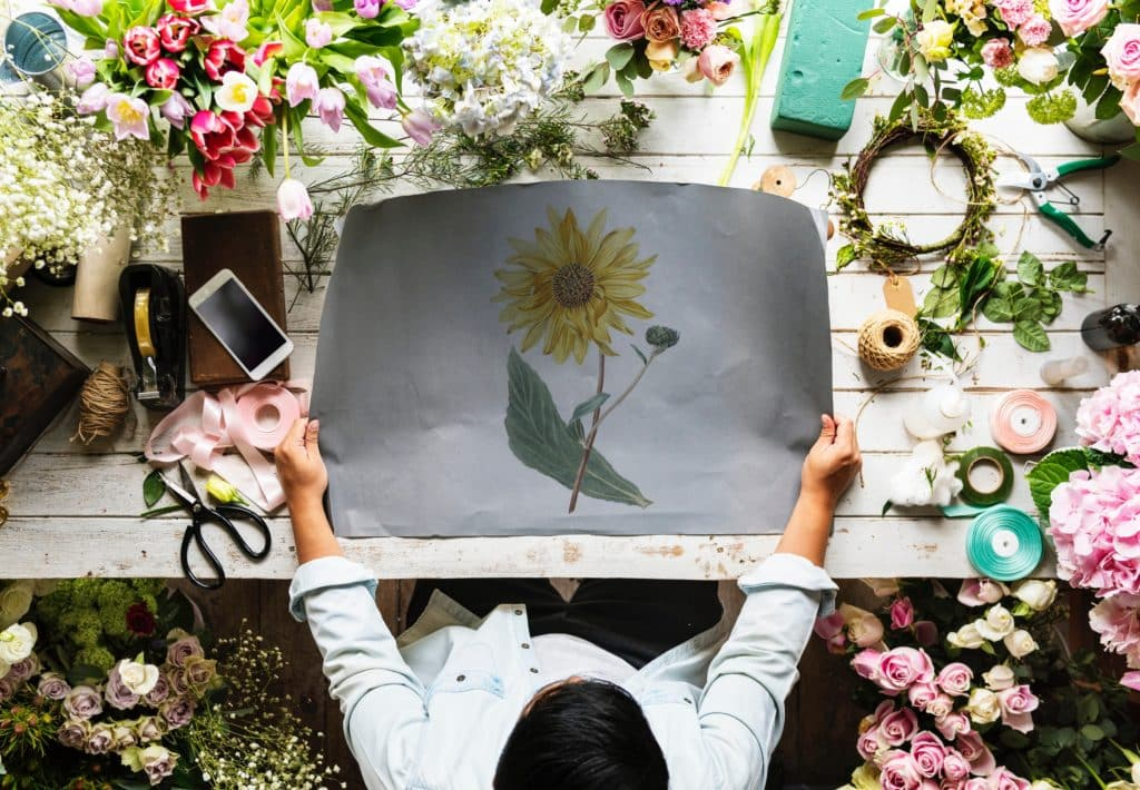 man standing in front of a drafting table covered in flowers and holding a large sketched drawing of a sunflower