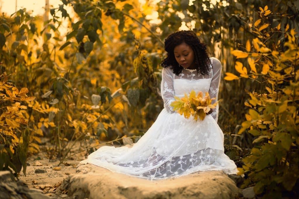 bride kneeling down picking up fall leaves