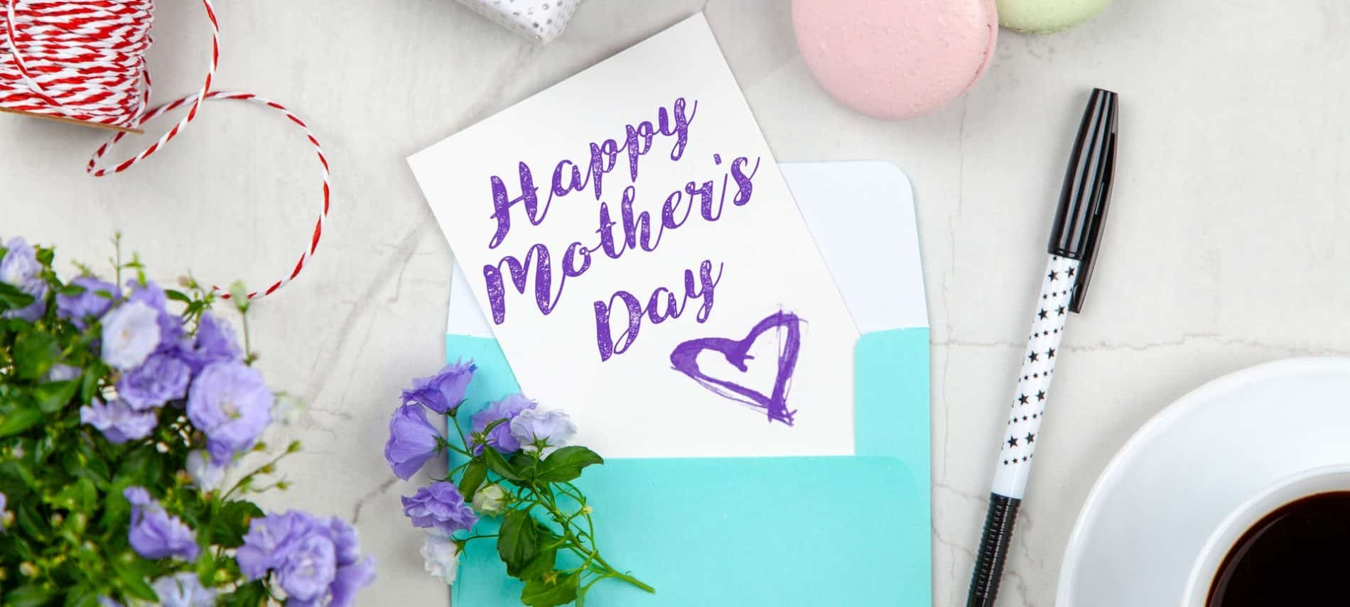 "card sticking out of a blue envelope with the words ""Happy Mother's Day"" written on it sitting on a table with flowers, a gift box, and macarons"