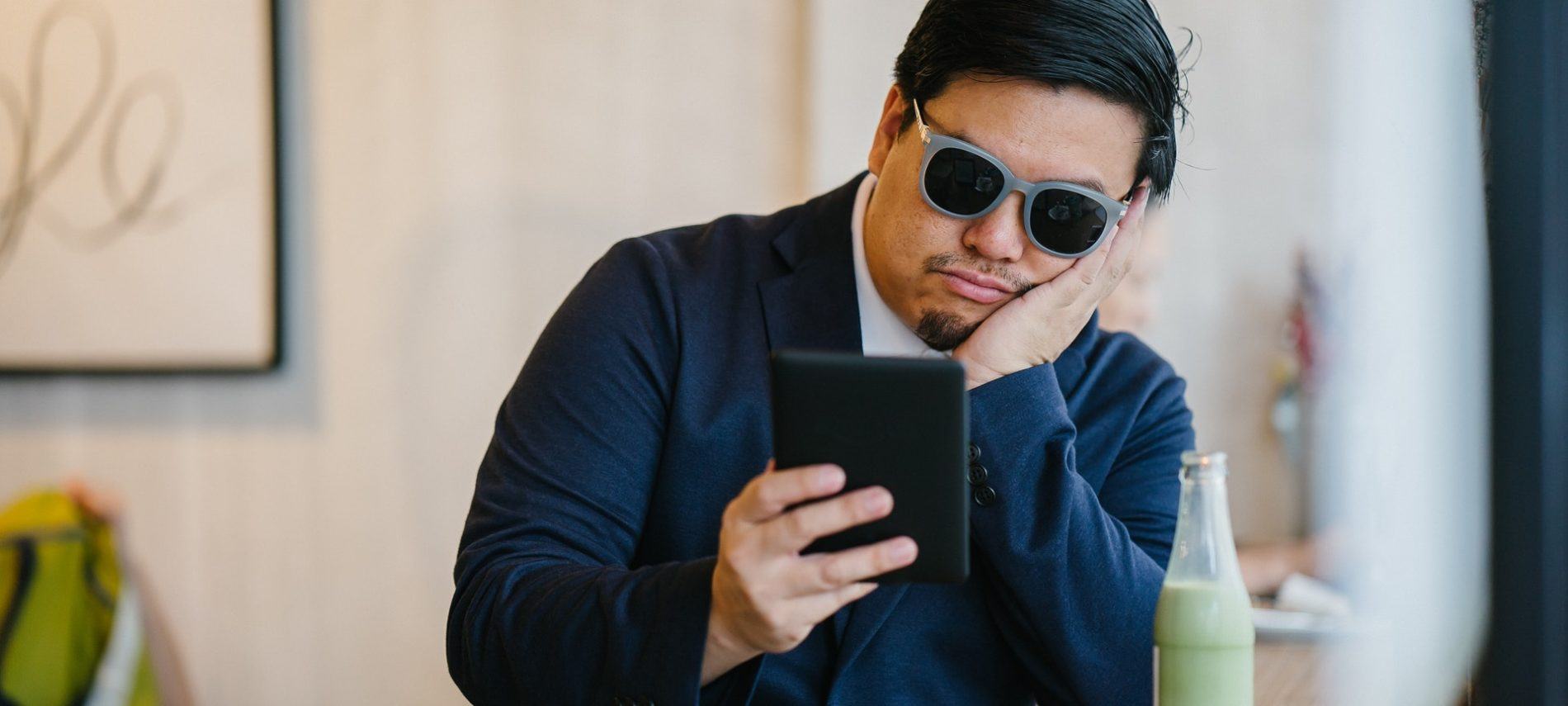 man sitting in a coffee shop looking at his phone looking bored