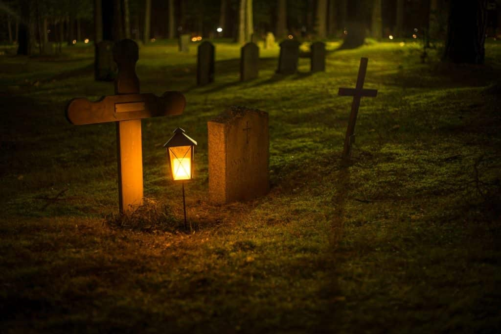 two headstones in a cemetery with a lantern