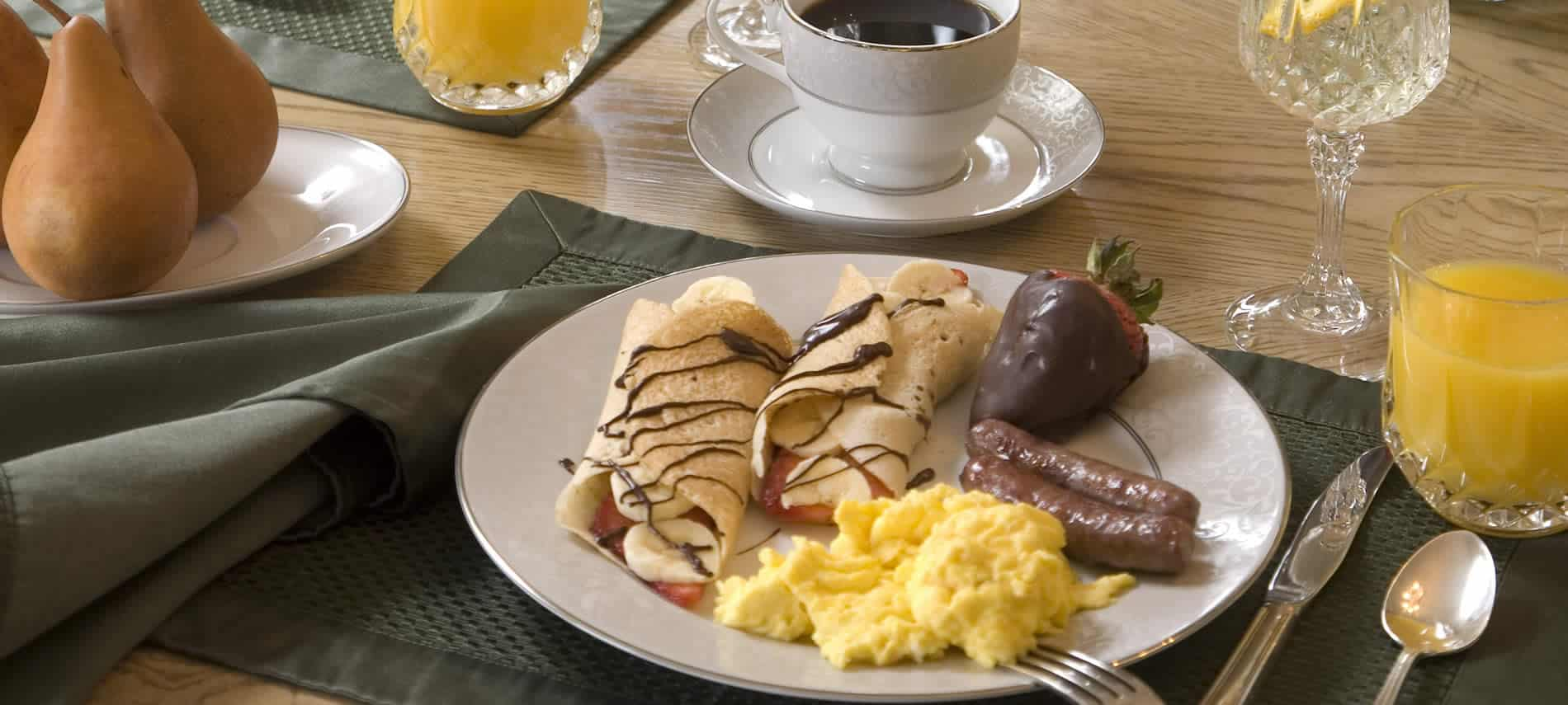 two crepes with chocolate drizzle on plate with scrambled eggs and sausage and chocolate dipped strawberry on plate on table next to coffee cup and glass of oj