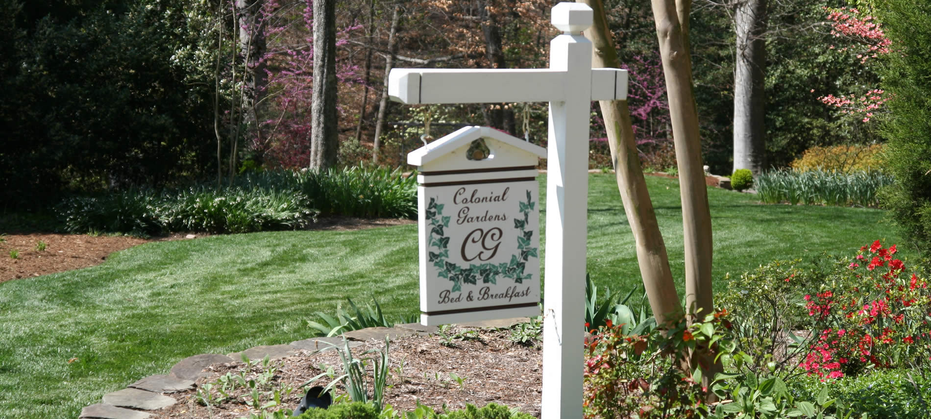 hanging wooden sign with the workds colonial gardens be and breakfast painted in white and green on yard with green lawn background