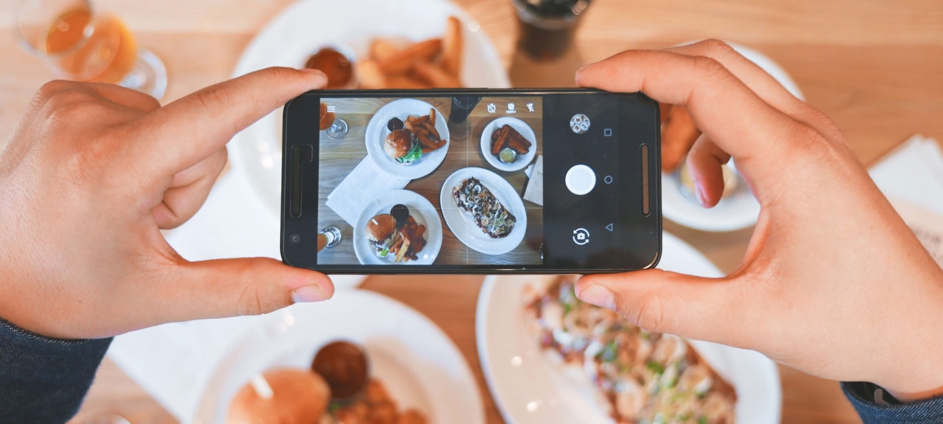someone holding a smart phone while taking a photo of a breakfast table with plates of breakfast foods