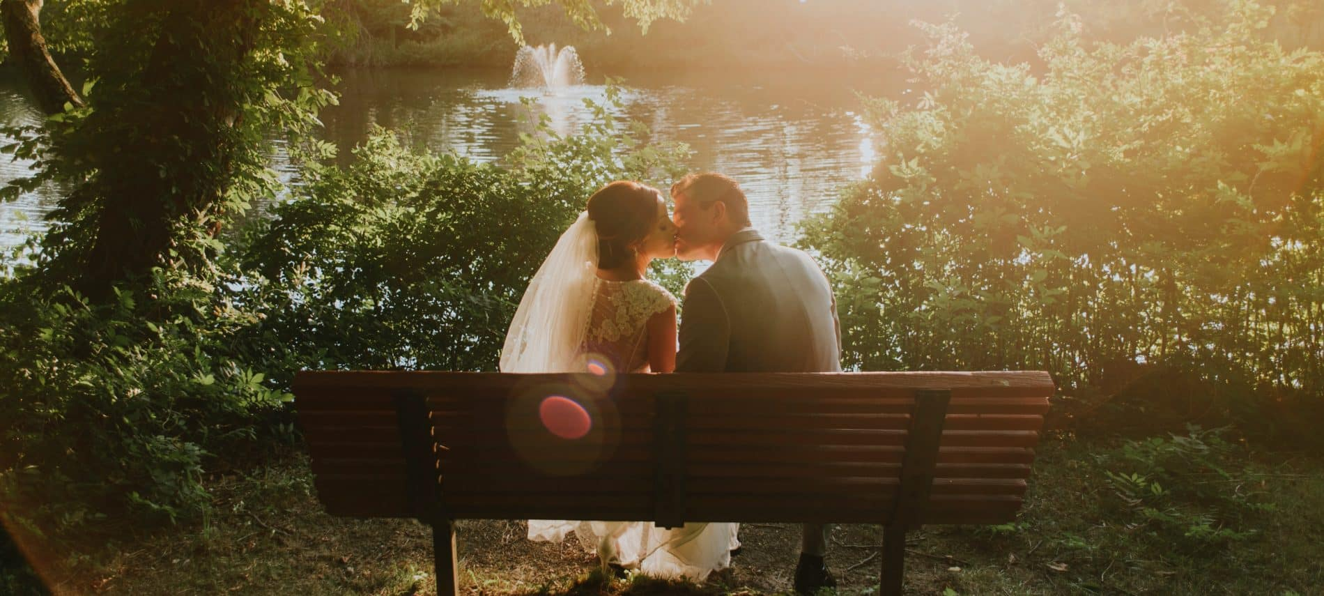 Bride and groom sitting on bench in park in front of lake kissing