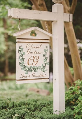 Painted white sign with colonial gardens and paintied leaves