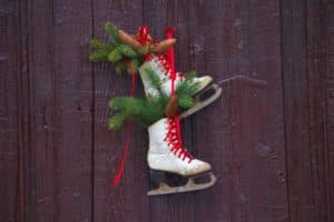 White figure skates with red laces hanging on a wooden wall with greenery tucked inside each one.