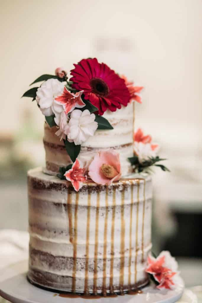 two tired naked wedding cake with pink and white flowers as decoration