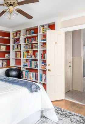 wall of books in front of queen sized bed