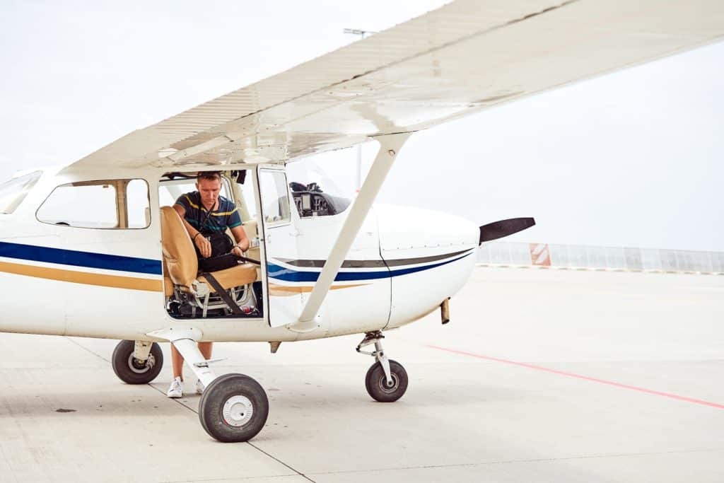 man preparing to fly in a white biplane