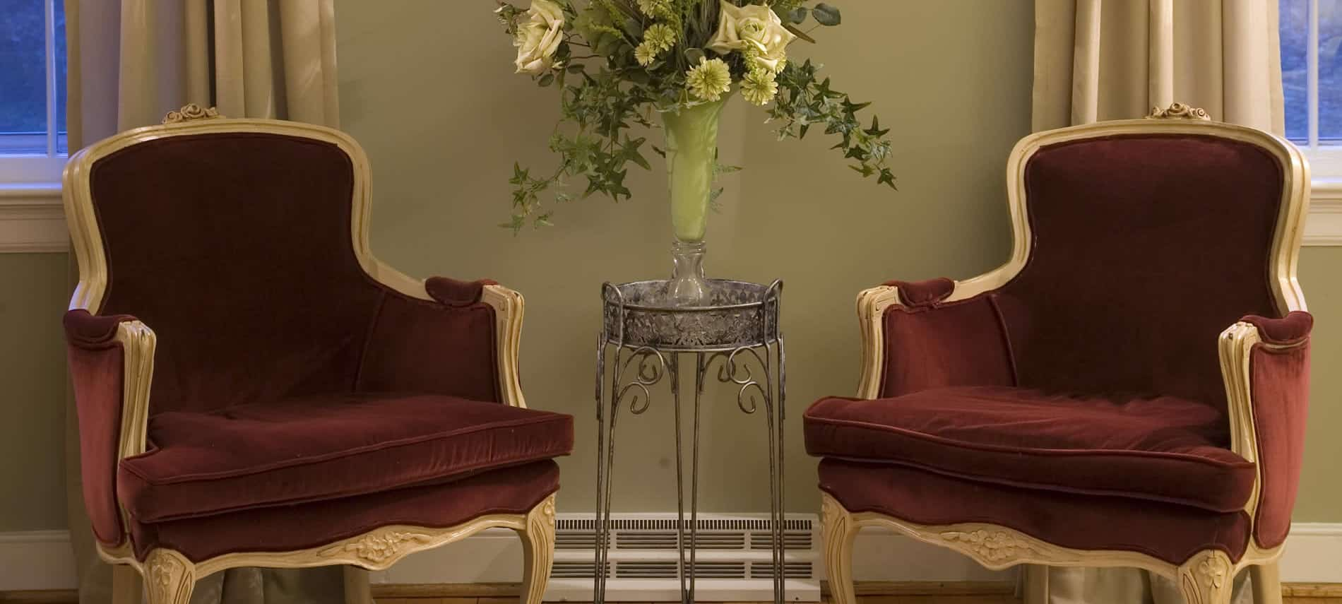 two red velvet ladies French barrel chairs with flower arrangement in middle on metal plant stand
