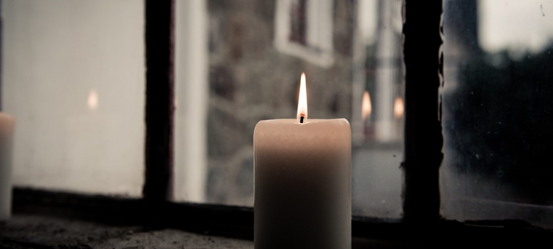 lighted cylinder candle in window looking out onto street scene at dusk