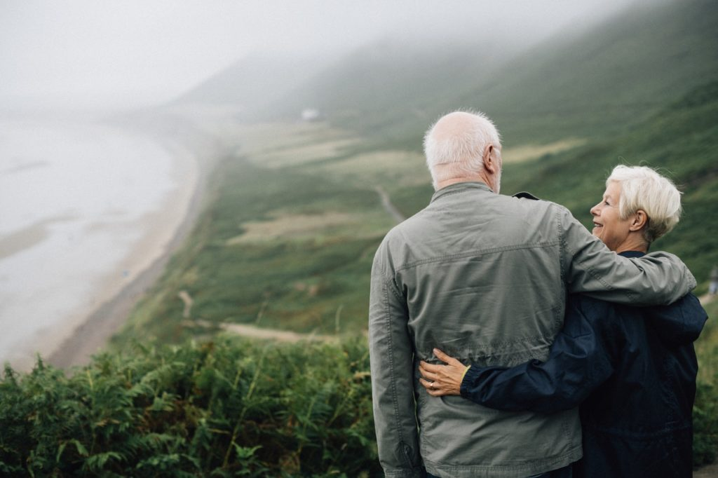 an older couple standing with their arms around each other overlooking a summer coastline in Ireland