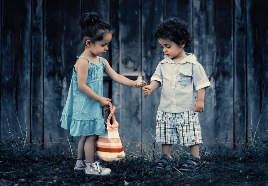 a little girl in a blue dress handing a dandelion flower to a little boy with curly brown hair