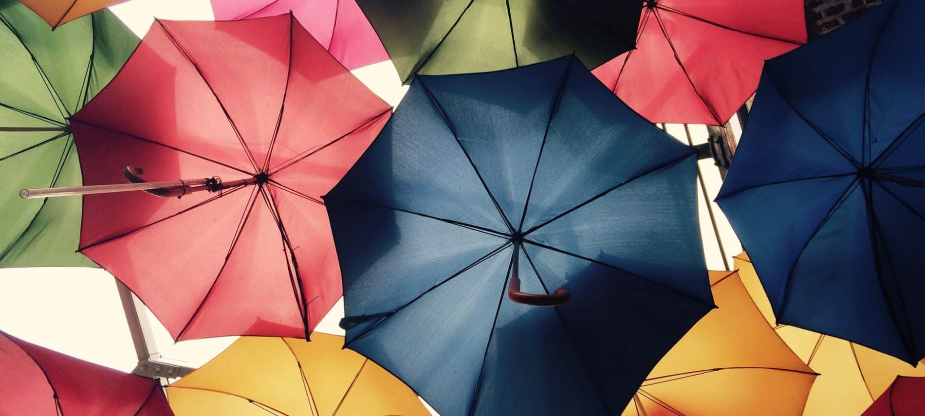 camera looking up at multiple multicolored open umbrellas with sky in the background