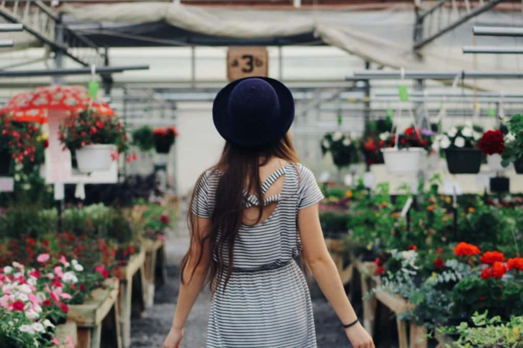 woman wearing a black hat and striped dress walking through a garden store surrounded by potted flowers and hanging plants