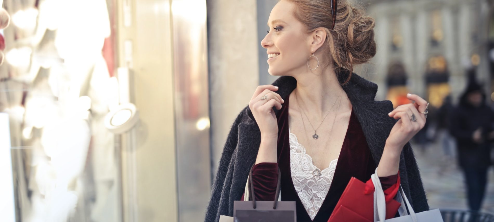 lady in white dress with black coat out side looking in window of storefront carrying bags