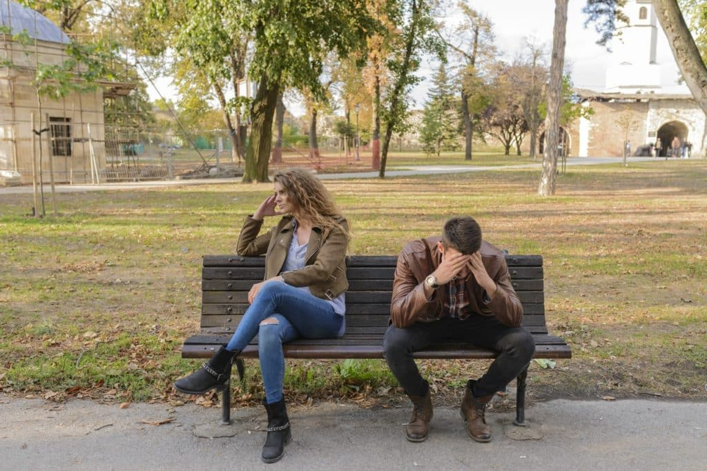 young man an woman sitting on a park bench facing away from each other in frustration