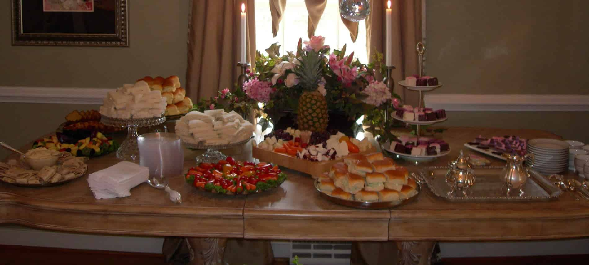 Table filled with trays of food including egg salad sandwiches petite fours on three tiered tray and flowers in front of window