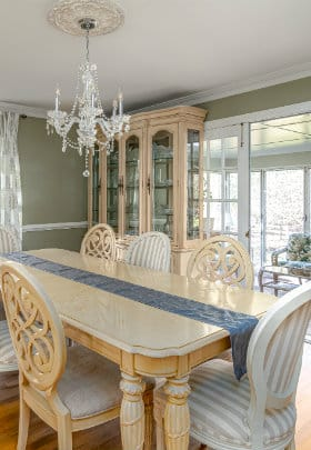 Blonde dinning room table with 8 chairs and china cabinet in front of entrance to sunroom