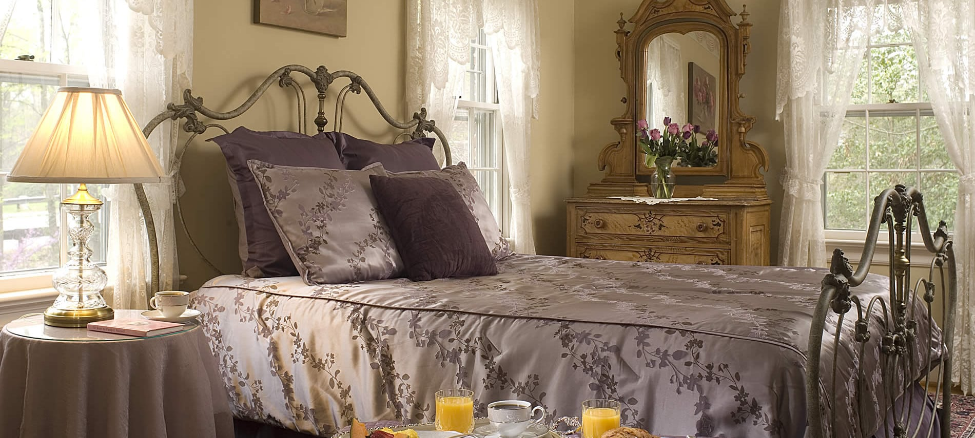 breakfast in room on tray next to queen sized bed with purple comforter and pillow shams light on side table illuminated