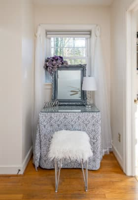 plush vanity table in front of window with fur seat and guilded sliver framed mirror