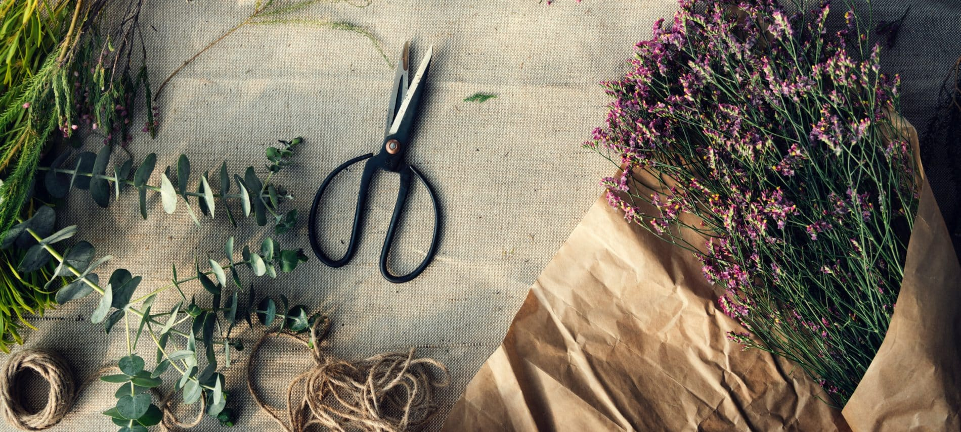 Flower shears lying on burlap covered table along side of eucalyptus and lavender with brown string and brown paper