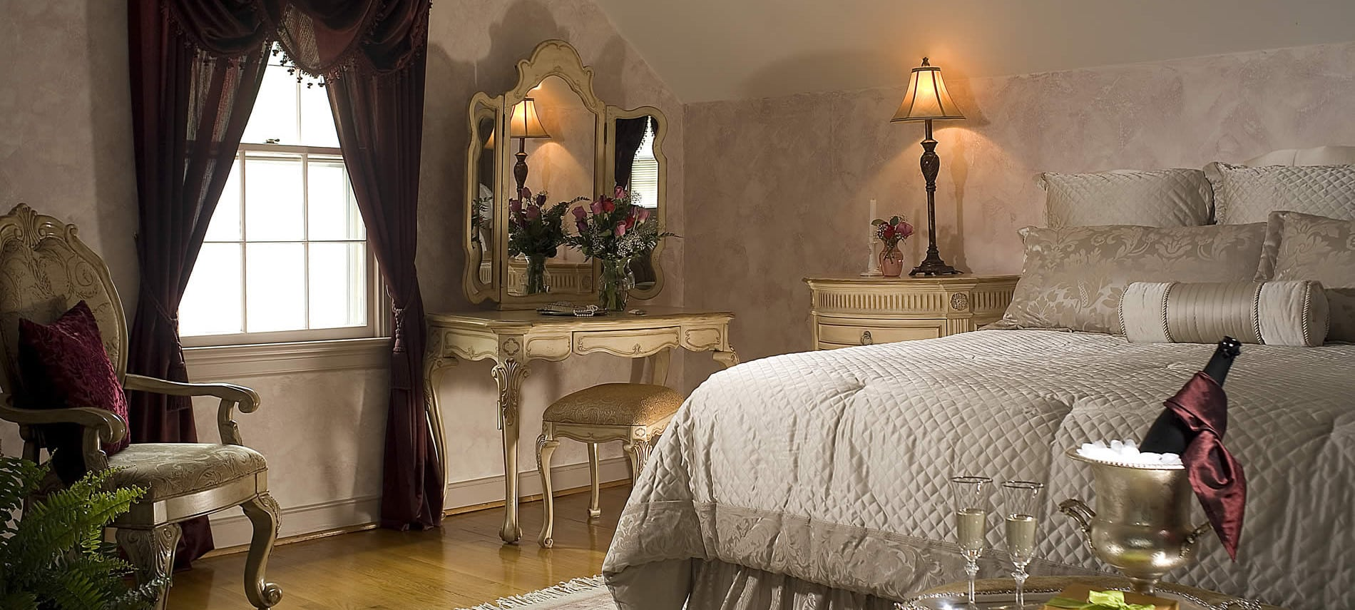 king bed with vanity and night stand with lighted lamp on top