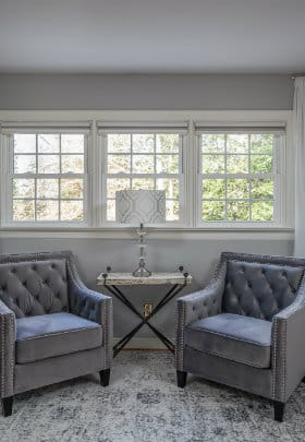2 gray velvet chairs with table and lamp on gray and white rug in rhododendron sitting alcove