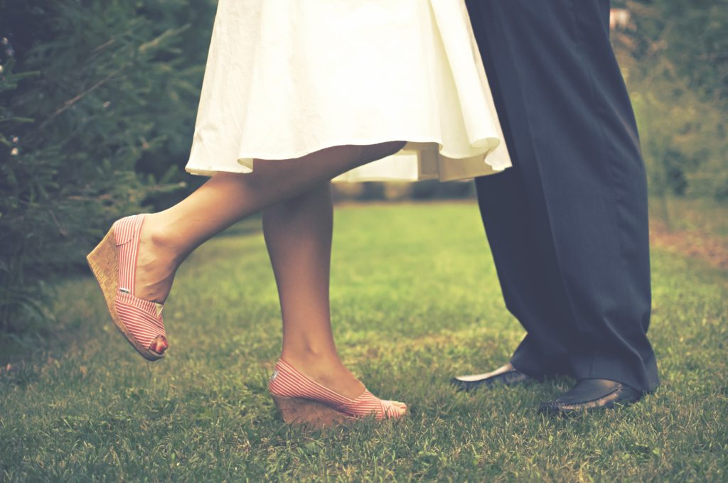 the feet of a bride and groom facing each other standing on a grassy yard