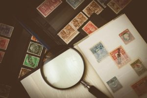 Stamp collection and magnifying glass on a table.