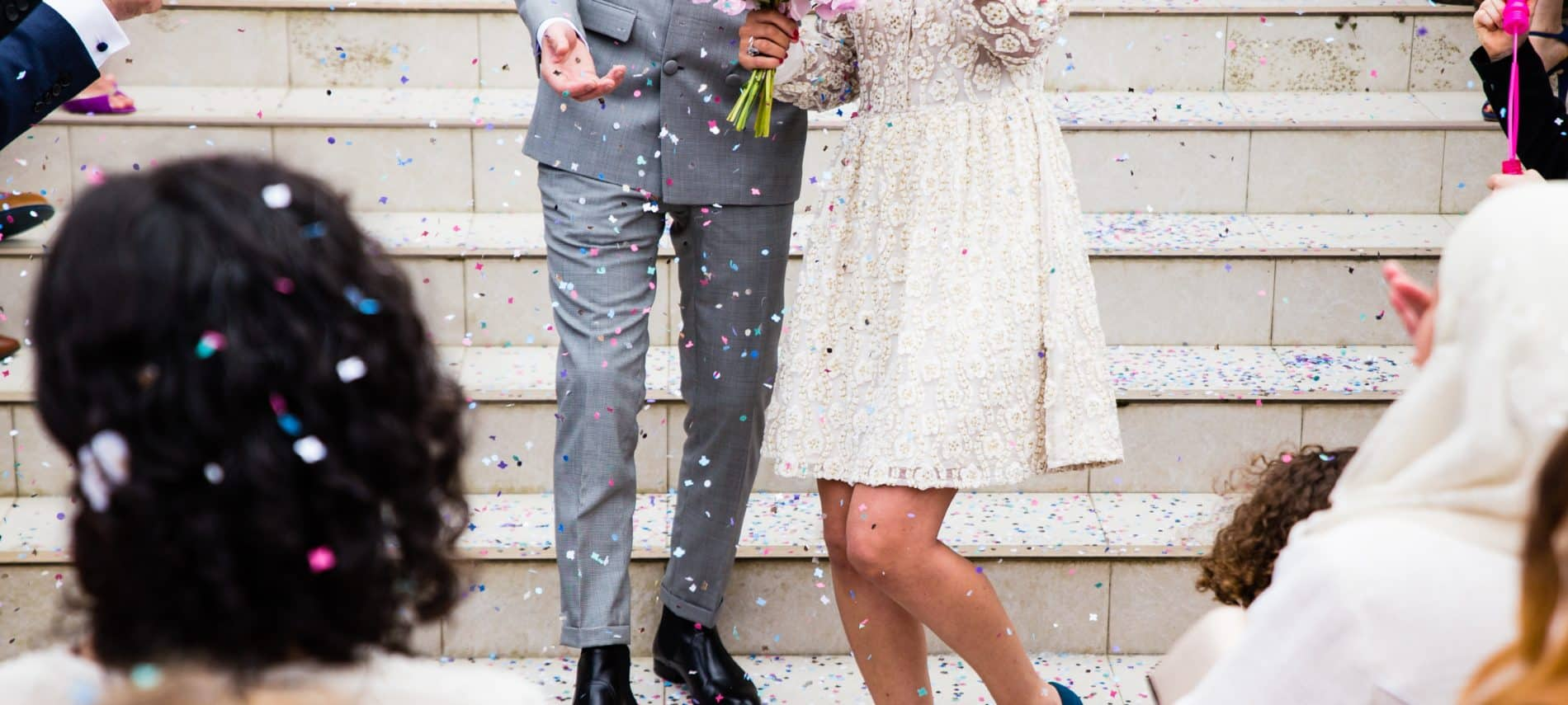 bride and groom standing on the steps of a church with friend surrounding them throwing confetti on them