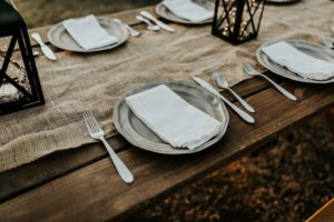 An outdoor table setting features neutral colors and lighted lantern centerpieces.
