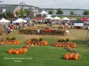 Grassy green field full of orange pumpkins, white vendor tents, haystacks and people